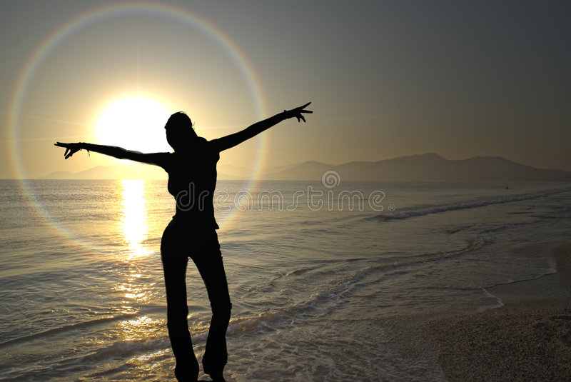 Celebrate. A young woman exults the onset of the vivid sunset in french riviera stock photo