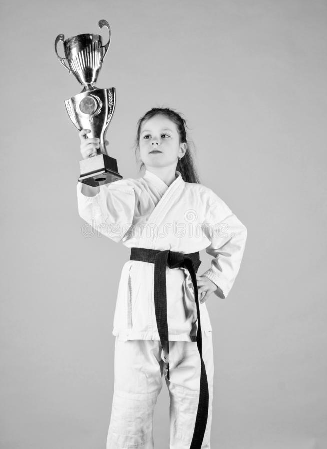 Celebrate achievement. Karate gives feeling of confidence. Strong and confident kid. Girl little child in white kimono. With belt. Karate fighter child. Karate royalty free stock photo