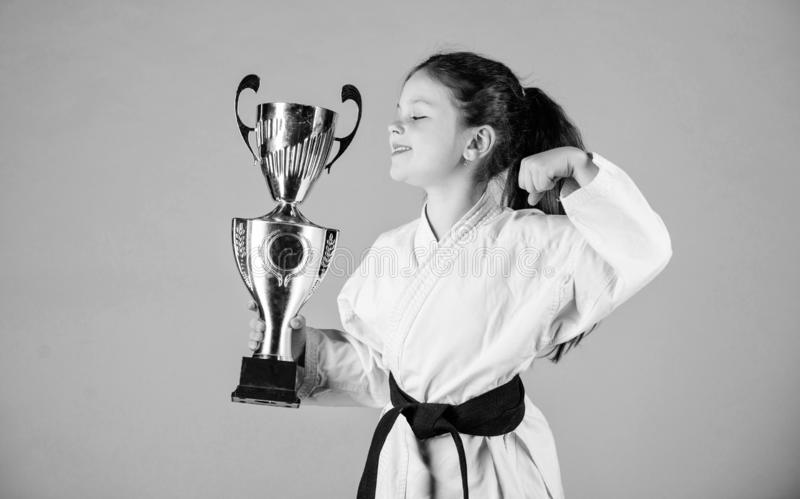 Celebrate achievement. Strong and confident kid. Girl little child in white kimono with belt. Karate fighter child. Karate sport concept. Self defence skills stock photos