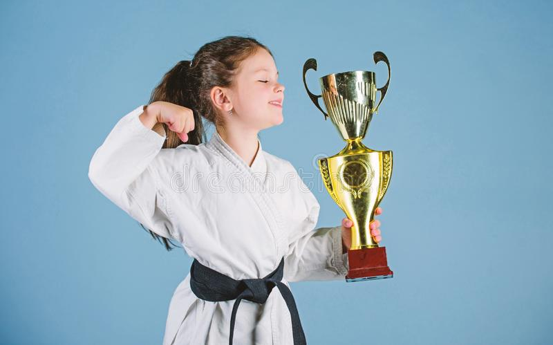 Celebrate achievement. Strong and confident kid. Girl little child in white kimono with belt. Karate fighter child. Karate sport concept. Self defence skills royalty free stock photos