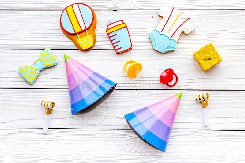 Celebrate child`s birthday. Cookies in shape of baby accesssories, party hats, gift box on white wooden background top royalty free stock image