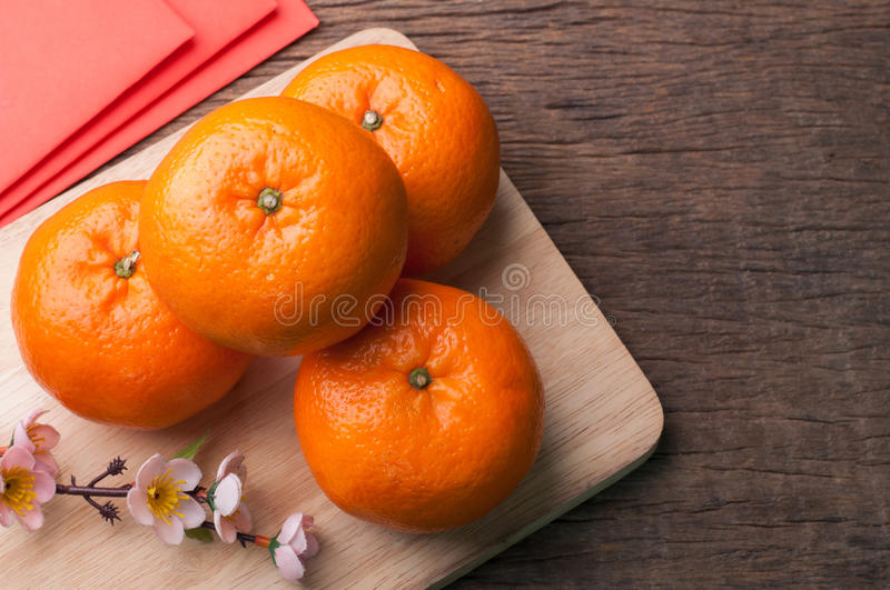 Celebrate Chinese New Year background with orange fruit for wars. Hip, red envelope and beautiful blossom stock photos