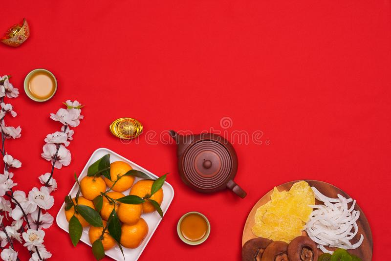 Celebrate Chinese New Year background with orange fruit for wars. Hip, red envelope and beautiful blossom royalty free stock image