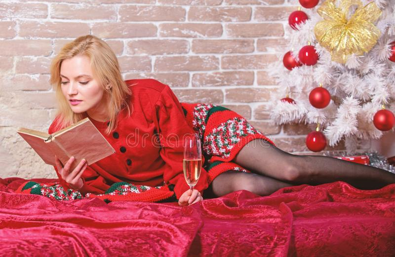 Celebrate christmas without social obligations. Woman hold glass champagne and book. Girl relax near christmas tree. Alone on christmas. Celebrating christmas stock photos