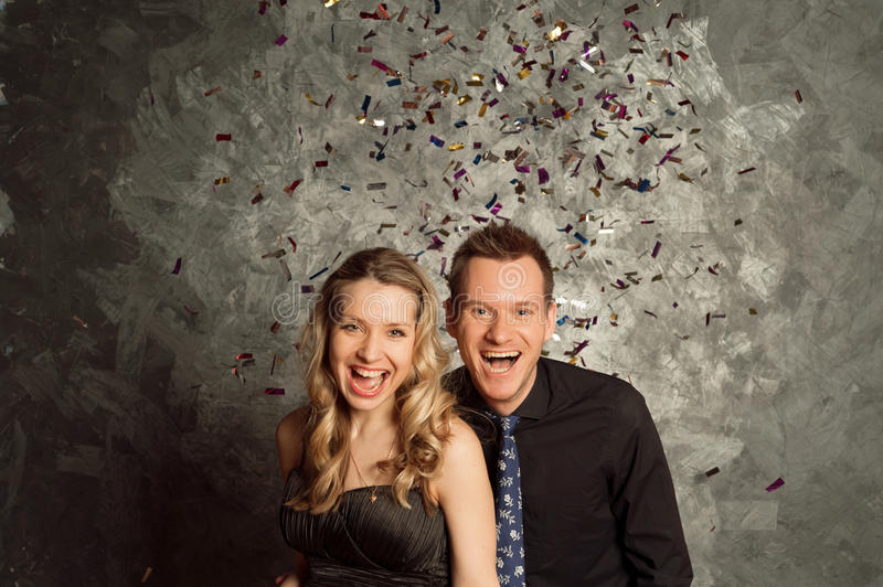 Celebrate holiday with tinsel salute, portrait of young couple. People celebrate holiday with tinsel salute, portrait of young men and women couple stock photos