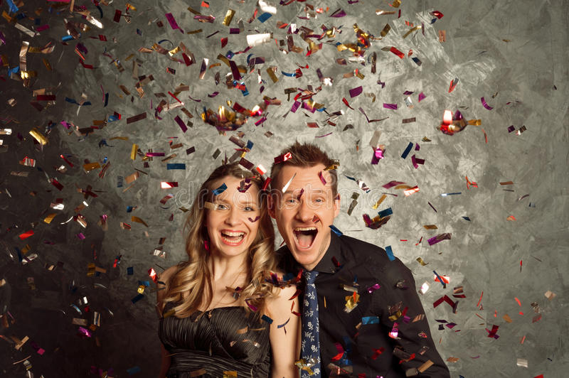 Celebrate holidays with tinsel salute, portrait of young couple. People celebrate holiday with tinsel salute, portrait of young men and women couple royalty free stock photos