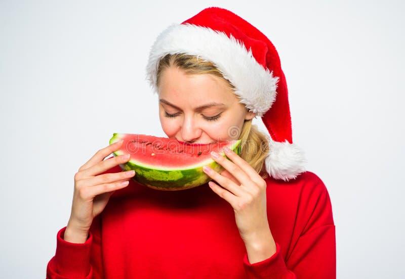 Celebrate new year exotic resort. Christmas girl eat watermelon. Girl santa hat eat watermelon white background. Ways. Enjoy tropical christmas. Exotic stock photos