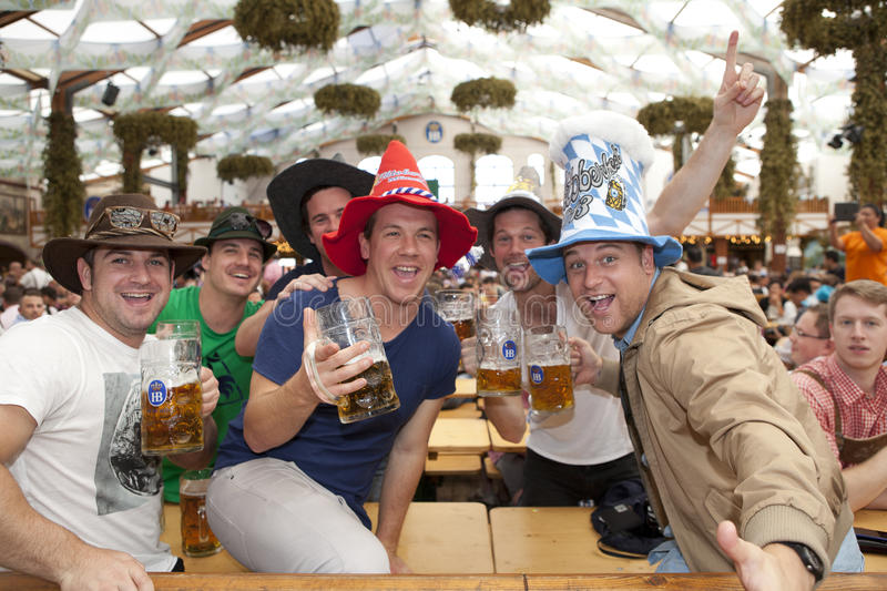 Celebrate Oktoberfest. Visitors sit in the tent at the Oktoberfest and beer in a beer mug stock image