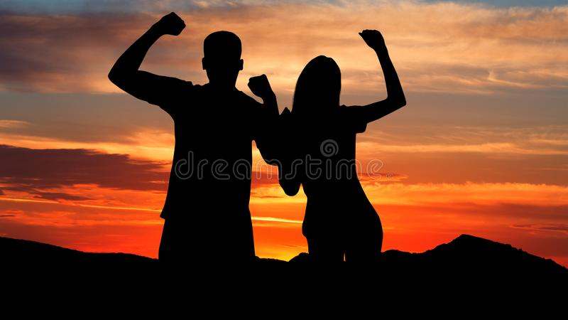 Celebrate success. Silhouette of couple against sunset stock image