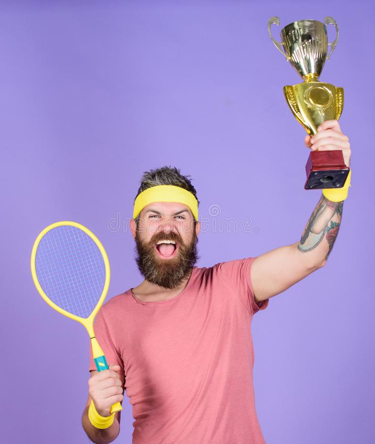 Celebrate victory. Tennis champion. Athletic man hold tennis racket and golden goblet. Win tennis game. Tennis player. Win championship. Man bearded successful stock image