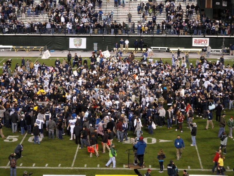 Celebratetion van de universiteitsvoetbal op het gebied na eind een spel royalty-vrije stock foto