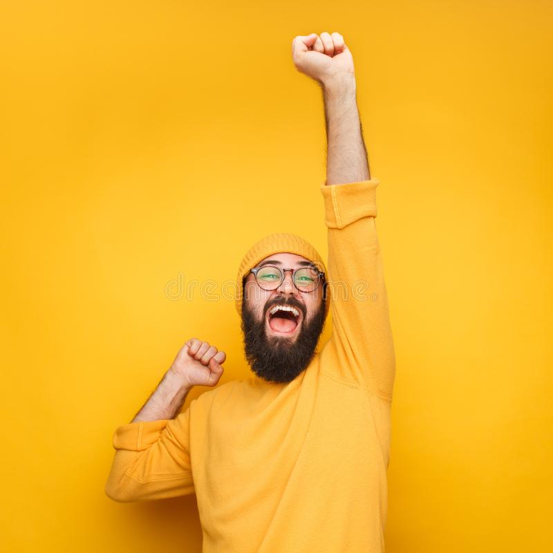 Celebrating bearded man with hand up. Happy celebrating bearded man in yellow hat posing with hands up stock photo