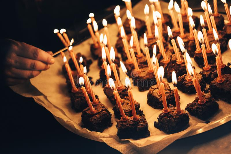 Celebrating birthday anniversary of older person with many candles burning on many small chocolate cake pieces royalty free stock photos