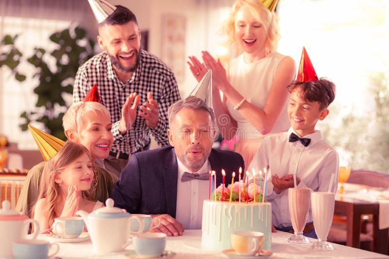 Aged man celebrating birthday with daughter and grandchildren stock image