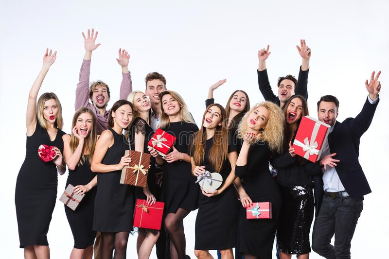 Friends in stylish clothes with gift boxes in hands having fun. royalty free stock images