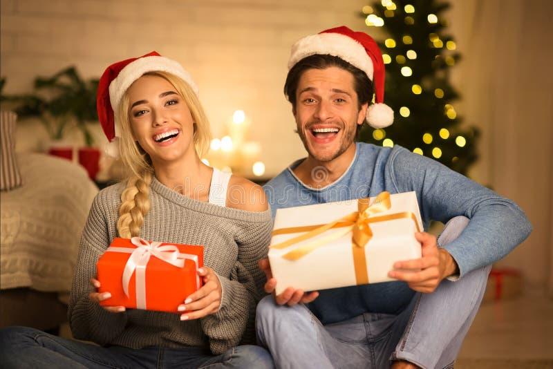 Celebrating Christmas together. Couple holding gift boxes royalty free stock photography