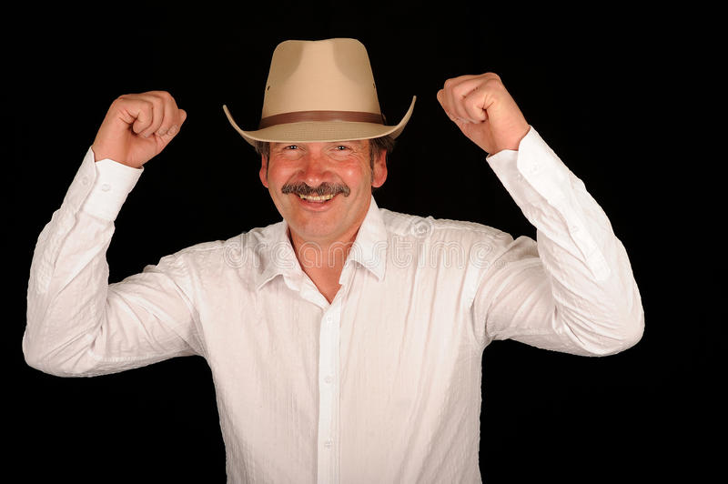 Celebrating cowboy. Half body portrait of smiling cowboy cheering with arms in air, black background royalty free stock photography