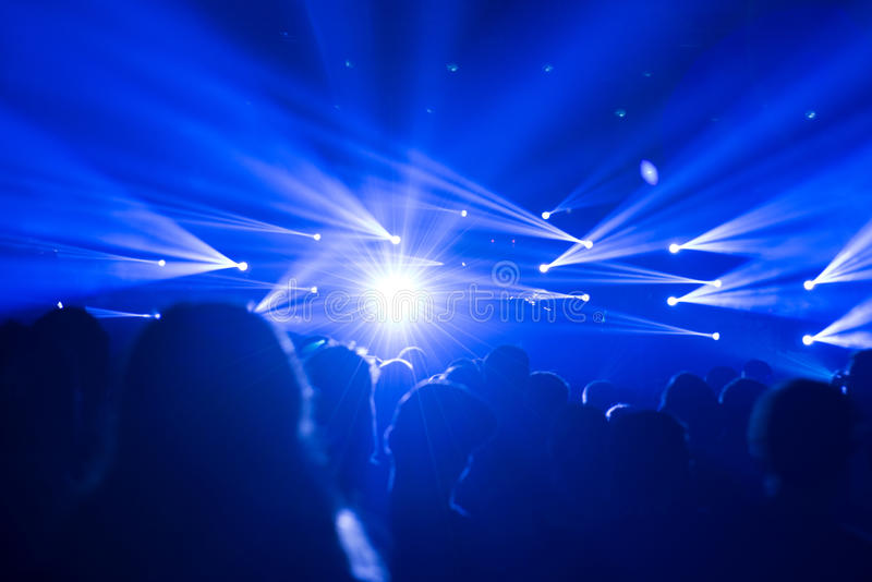 Celebrating crowd with blue lights at a concert - festival. Large crowd of people at a festival or party celebrating a great event stock photography