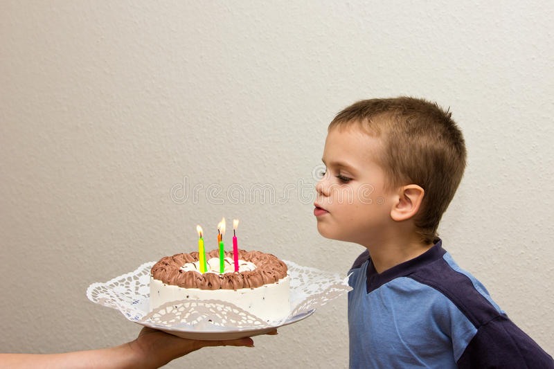 Celebrating fifth birthday boy cake son blowing candle stock photography