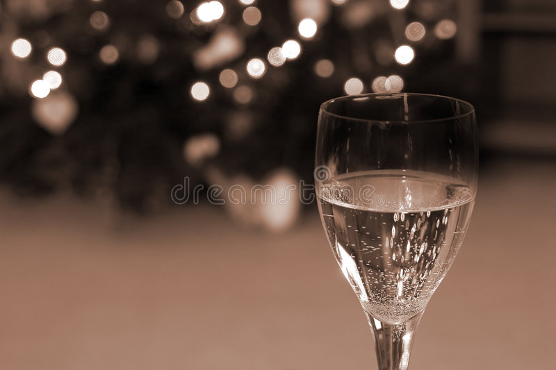 Celebrating the Holidays. Close up on a Wine Glass with the Christmas lights on the background royalty free stock images