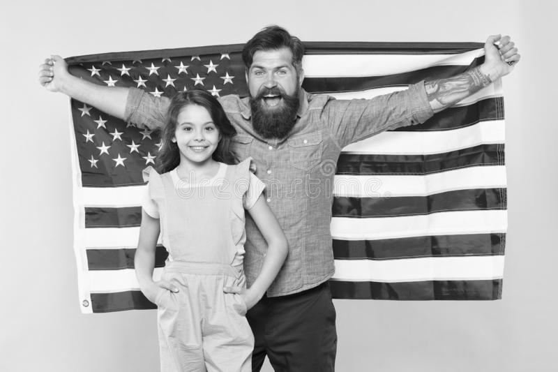 Celebrating the Independence every July 4th. Happy family commemorating anniversary of nations independence. Father and. Little child holding american flag on royalty free stock photos