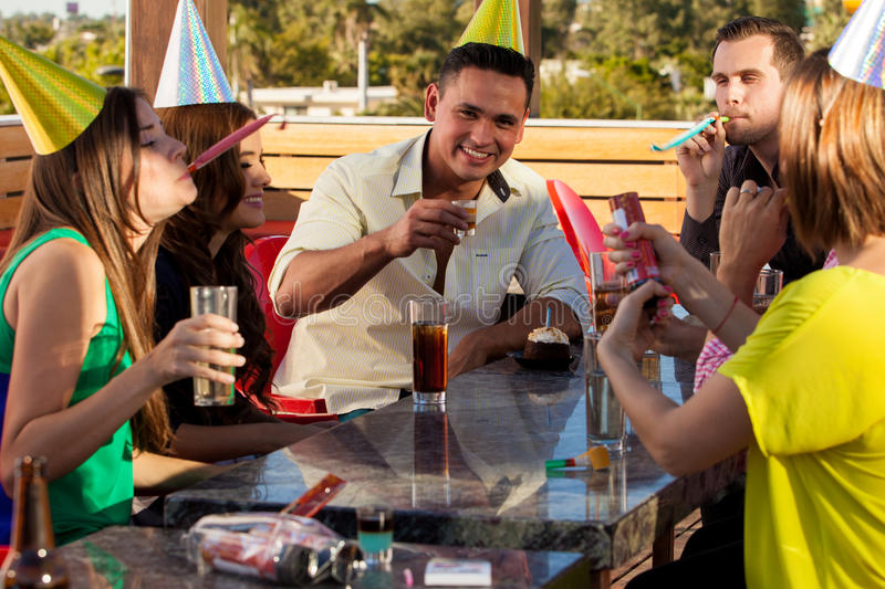 Celebrating my birthday at a bar. Young Hispanic men and his friends wearing party hats and celebrating his birthday with drinks and noisemakers stock image