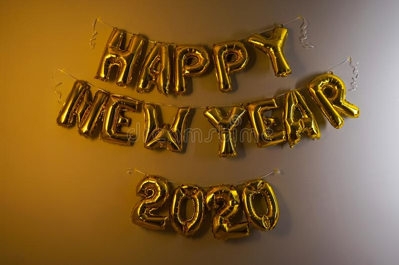 Celebrating the New Year 2020. Gold foil balloons on a gray background. Foil balls royalty free stock photos