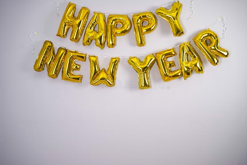 Celebrating the New Year. Gold foil balloons on a gray background. Foil balls, place for text royalty free stock images