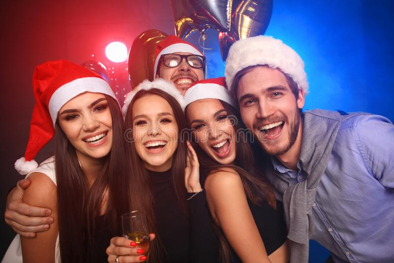 Celebrating New Year together. Group of beautiful young people in Santa hats throwing colorful confetti, looking happy. Celebrating New Year together. Group of royalty free stock photography