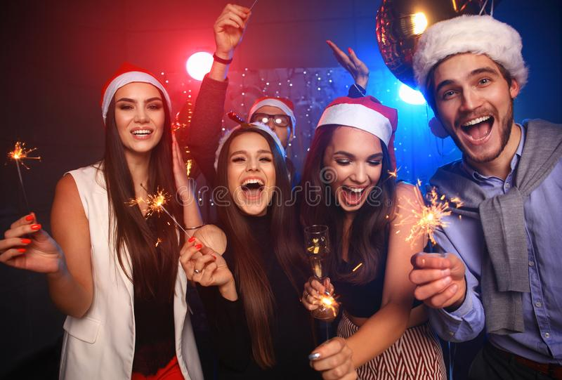 Celebrating New Year together. Group of beautiful young people in Santa hats throwing colorful confetti, looking happy. Celebrating New Year together. Group of stock photos