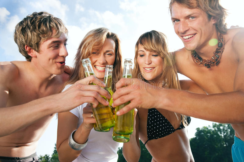 Celebrating party at beach. Group of very beautiful people celebrating on the beach in the summer of their lives - focus on bottles stock photo