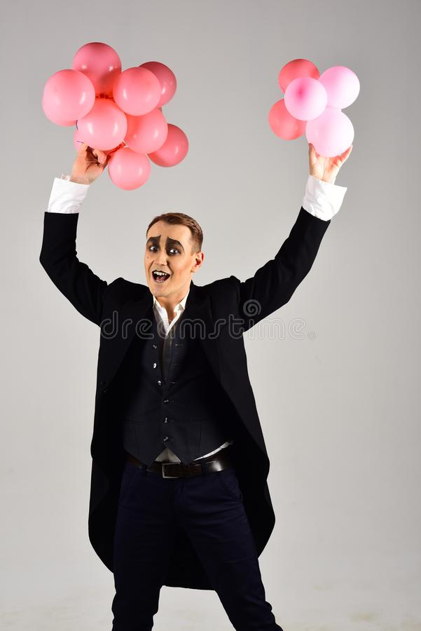 Celebrating the special day. Man with mime makeup on birthday party. Balloon artist. Mime man with party balloons. Happy stock images
