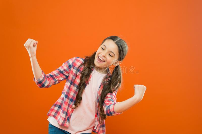 Celebrating success. happy childrens day. childhood happiness. little girl orange background. kid fashion. smiling royalty free stock photography