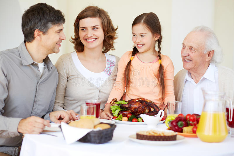 Celebrating Thanksgiving Day. Happy family at Thanksgiving table going to eat roasted turkey held by cute girl stock photo