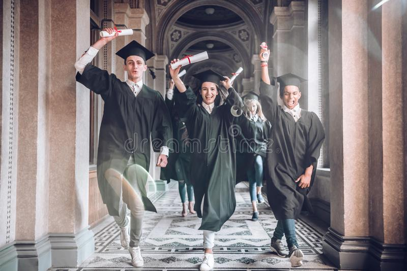 Celebrating their achievements together.University was the best years of their lives!Group of smiling university students holding royalty free stock photography