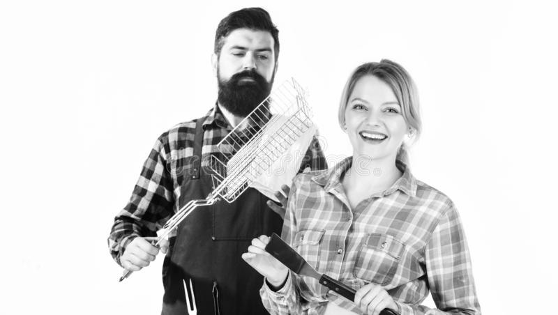 Celebrating their friendship. Tools for roasting meat. Man bearded hipster and girl. Preparation. Family weekend. Couple royalty free stock photo