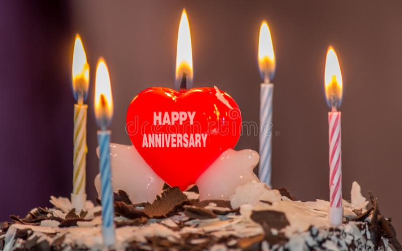 Celebrating wedding anniversary with a beautiful heart shape candle on cake royalty free stock photography