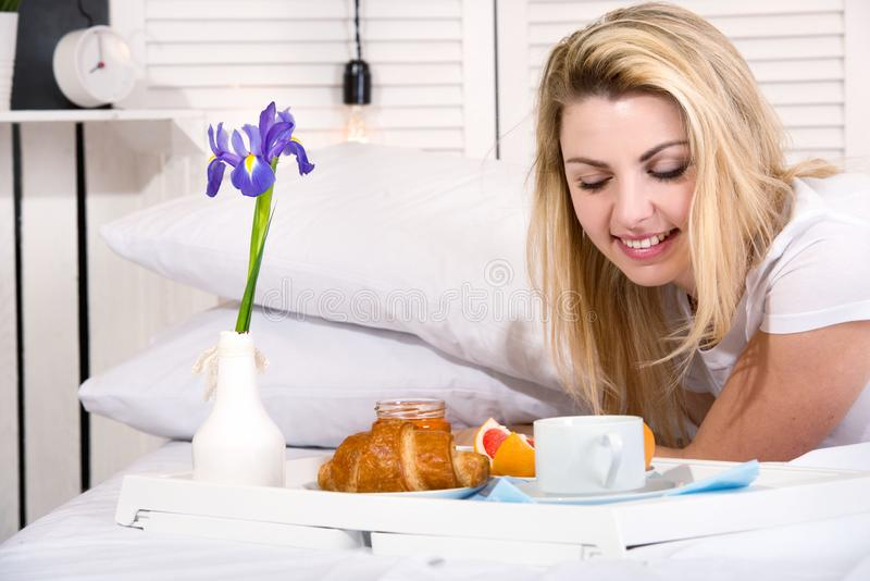 Beautiful young woman having breakfast in bed. Surprise from beloved husband. Celebrating a woman`s day, mother`s day. Celebrating a woman`s day, mother`s day stock photos