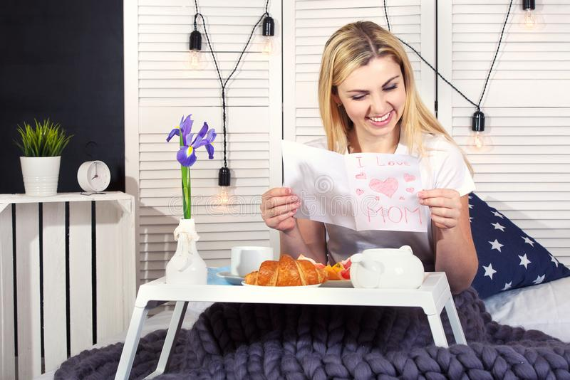 Beautiful young woman having breakfast in bed. Surprise from beloved son. Celebrating a woman`s day, mother`s day. Celebrating a woman`s day, mother`s day royalty free stock image