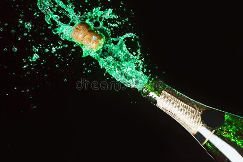 Celebration alcohol theme with explosion of splashing green absinth on black background. royalty free stock photography