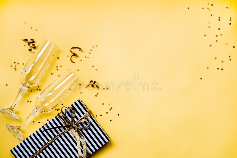 Celebration background - top view of two chrystal champagne glasses, a gift box wrapped in black and white striped paper, ribbons. And star shaped golden royalty free stock photos