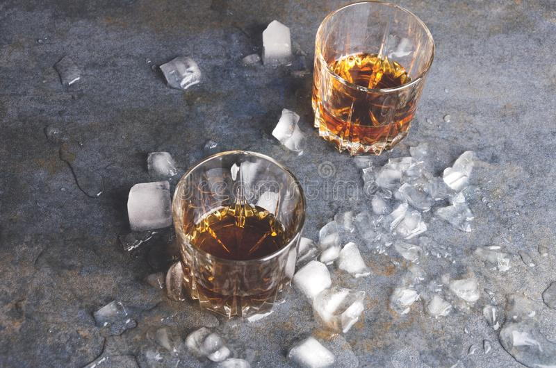 Celebrating at the bar. Pair of glasses with whisky and pieces of ice on gray table. Celebration at the bar.Pair of glasses with alcohol drinks and ice cubes stock photos