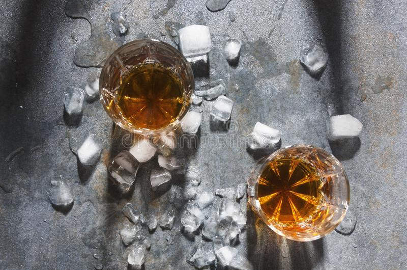 Celebration at the bar.Pair of glasses with alcohol drinks and ice cubes, top view. Glasses with whisky served in the unusual way. On grey table Celebration at royalty free stock photo