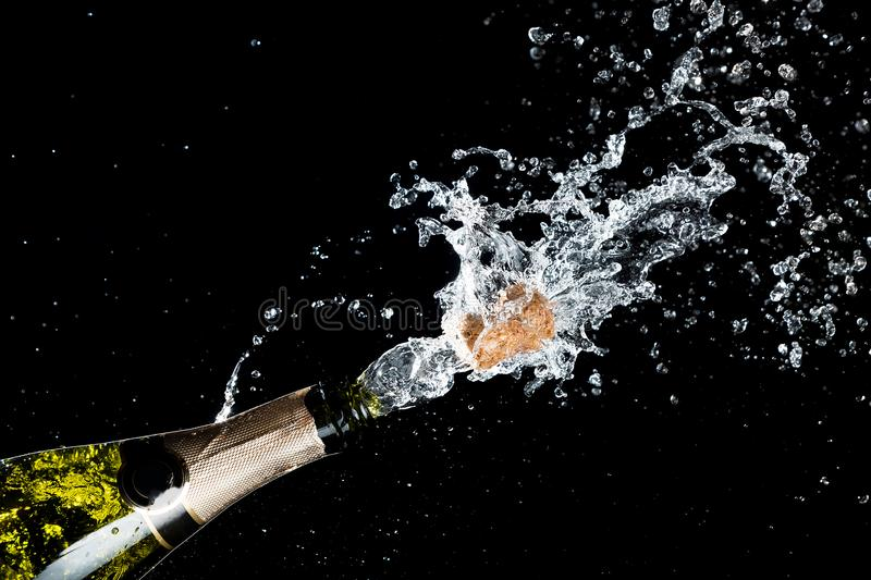 Celebration of birthday, anniversary or Christmas theme. Explosion of splashing champagne sparkling wine with flying cork out of t stock photography
