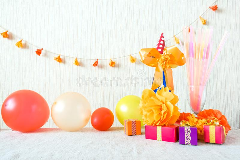 Celebration, Birthday party background with colorful party hat, confetti, gift boxes and other decor. Colorful accessories for parties on wooden table. Copy stock photography
