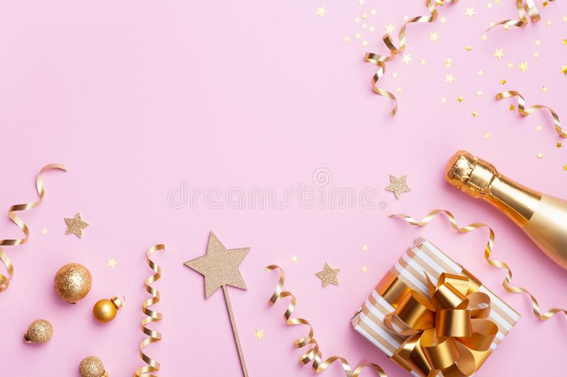 Celebration Christmas or New year background. Champagne bottle, gift or present box and golden confetti on pink top view. Flat lay royalty free stock photos