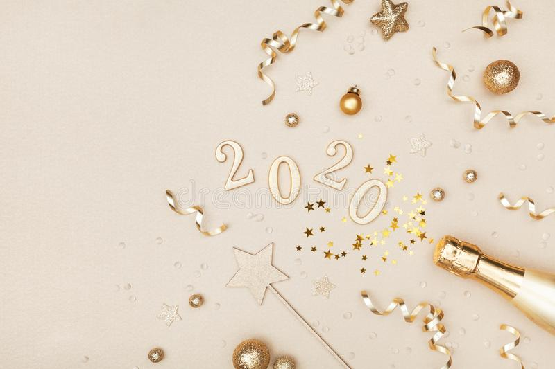 Celebration Christmas and New Year background with golden champagne bottle, holiday decoration, confetti stars and 2020 numbers. Flat lay style stock images