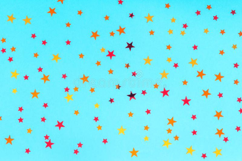 Celebration concept. Photo of multicolored stars sprinkles on blue backdrop. Festive holiday background for your projects. royalty free stock image