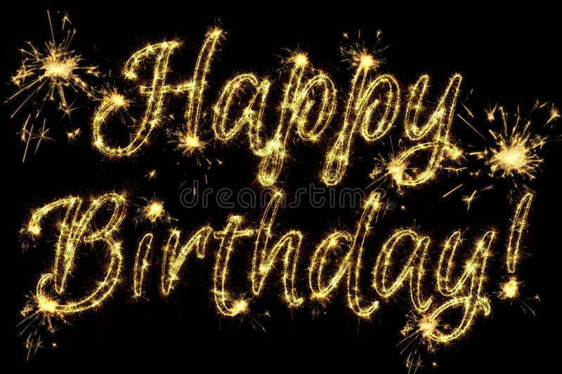 Celebration concept. Text Happy Birthday written sparkling sparklers isolated on black background. Overlay template for greeting royalty free stock image