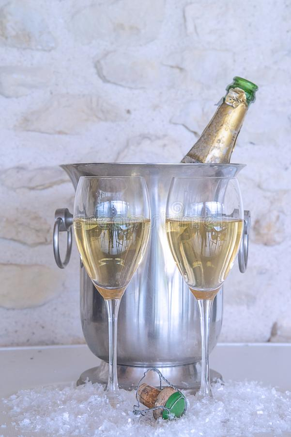 Celebration concept: two glasses of champagne and vintage bottle in the bucket. Two glasses of champagne and vintage bottle in the bucket royalty free stock photography
